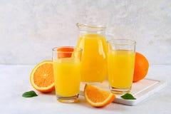 Tazas de cristal y una jarra de zumo de naranja fresco con las rebanadas de tubos anaranjados y amarillos en una tabla gris clara Foto de archivo libre de regalías