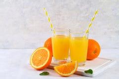 Tazas de cristal y una jarra de zumo de naranja fresco con las rebanadas de tubos anaranjados y amarillos en una tabla gris clara Foto de archivo
