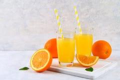 Tazas de cristal y una jarra de zumo de naranja fresco con las rebanadas de tubos anaranjados y amarillos en una tabla gris clara Fotografía de archivo libre de regalías
