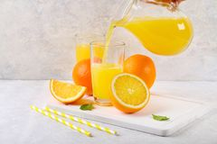 Tazas de cristal y una jarra de zumo de naranja fresco con las rebanadas de tubos anaranjados y amarillos en una tabla gris clara Imagenes de archivo