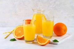 Tazas de cristal y una jarra de zumo de naranja fresco con las rebanadas de tubos anaranjados y amarillos en una tabla gris clara Fotos de archivo libres de regalías