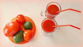 2 tazas de jugo de tomate y un poco de tomates y aguacate en la tabla Fotografía de archivo libre de regalías