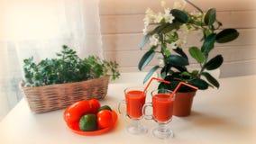 2 tazas de jugo de tomate y un poco de tomates y aguacate en la tabla en un fondo de flores Fotografía de archivo