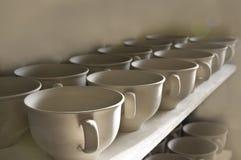 Tazas de la cerámica de Unfired en fila Fotos de archivo