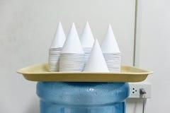 Tazas de papel disponibles de la forma de cono en la bandeja amarilla clara imagen de archivo