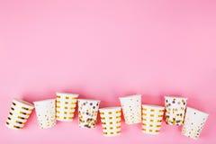Tazas de papel en fondo rosado fotografía de archivo libre de regalías