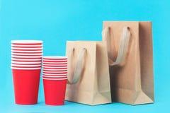 Tazas de papel y bolsos rojos del eco en fondo azul fotos de archivo libres de regalías