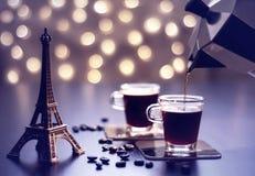 Tazas de recuerdo de la torre Eiffel del witn del café en una tabla y un bokeh hermoso del oro fotos de archivo