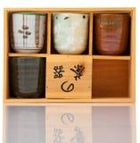 Tazas de té asiáticas de la cerámica fijadas en el caso de madera Imagen de archivo