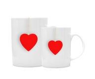 Tazas de té blancas con el tealabel rojo aislado en blanco Foto de archivo libre de regalías