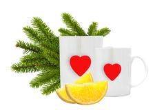 Tazas de té blancas con la etiqueta roja, las rebanadas del limón y la Navidad verde Imagen de archivo libre de regalías