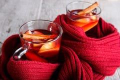 Tazas de té calientes del primer y bufanda roja en un fondo de madera Té y bufanda caliente Invierno acogedor Foto de archivo libre de regalías