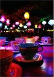 Tazas de té coloreadas multi en la tabla contra las lámparas iluminadas que cuelgan de techo en casa Fotografía de archivo