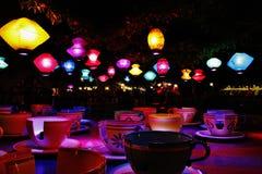 Tazas de té coloreadas multi en la tabla contra las lámparas iluminadas que cuelgan de techo en casa Imágenes de archivo libres de regalías