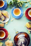 Tazas de té con las flores de las tortas y del pote y de las rosas del té en fondo elegante lamentable de los azules turquesa Foto de archivo libre de regalías