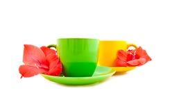 Tazas de té con las flores en un fondo blanco Fotos de archivo libres de regalías