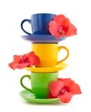 Tazas de té con las flores en un fondo blanco Foto de archivo libre de regalías