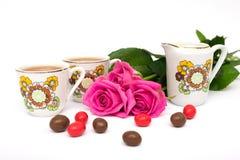 Tazas de té, de caramelos y de rosas Imágenes de archivo libres de regalías