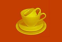 Tazas de té de cerámica amarillas con los platillos en fondo anaranjado del color Foto de archivo libre de regalías