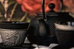 Tazas de té del hierro y pote apilados del té imagenes de archivo