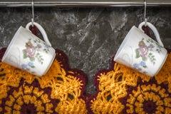 Tazas de té en la pared de la cocina Fotografía de archivo