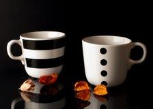 Tazas de té en un fondo negro Imagen de archivo