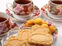 Tazas de té de la porcelana con té caliente y con el estampado de flores, las galletas y la placa con los albaricoques salvajes e Imagen de archivo libre de regalías