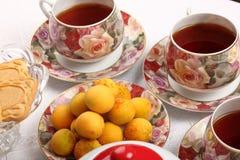 Tazas de té de la porcelana con té caliente y con el estampado de flores, la tetera, las galletas y la placa con los albaricoques Imagen de archivo