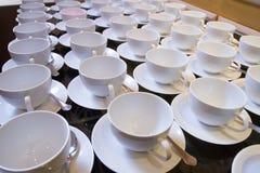 Tazas de té vacías apiladas con las cucharillas en una función sobre los vagos blancos Imagenes de archivo