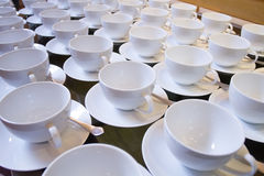 Tazas de té vacías apiladas con las cucharillas en una función sobre los vagos blancos Fotografía de archivo libre de regalías