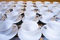 Tazas de té vacías apiladas con las cucharillas en una función sobre los vagos blancos Imágenes de archivo libres de regalías