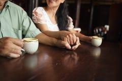 Tazas de té y manos el sostenerse Foto de archivo libre de regalías