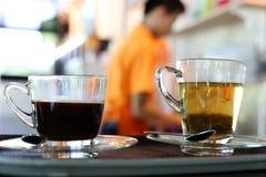 Tazas de té y tazas de café en la bandeja Imagenes de archivo