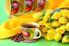 Tazas de té y tulipanes amarillos Imágenes de archivo libres de regalías