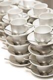 Tazas de té vacías empiladas con las cucharillas Imágenes de archivo libres de regalías