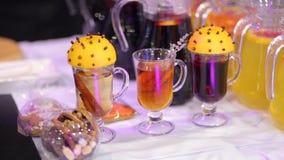 Tazas de vino reflexionado sobre con la rebanada de naranja y de canela Humor de la Navidad metrajes