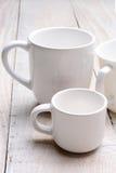 Tazas de Whie en el fondo blanco Foto de archivo libre de regalías