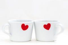 Tazas del café con leche con los corazones rojos Imagenes de archivo