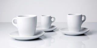 Tazas del café con leche en el fondo blanco Fotografía de archivo