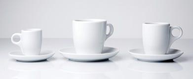Tazas del café con leche en el fondo blanco Imagen de archivo