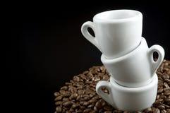 Tazas del café express en los granos de café Fotos de archivo libres de regalías