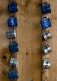 Tazas del estaño en una pared de madera Fotografía de archivo libre de regalías