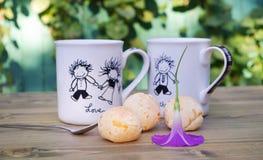Tazas divertidas en la tabla Bollo fresco en una placa Té que bebe en el medio de un día soleado Imagenes de archivo