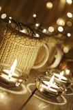 Tazas elegantes de cerámica en suéteres y guirnalda retra de la Navidad en fondo de las luces del bokeh Profundidad del campo baj Imagen de archivo libre de regalías