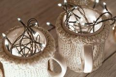 Tazas elegantes de cerámica en suéteres y guirnalda retra de la Navidad en fondo de las luces del bokeh Profundidad del campo baj Imágenes de archivo libres de regalías