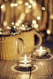 Tazas elegantes de cerámica en suéteres y guirnalda retra de la Navidad en fondo de las luces del bokeh Profundidad del campo baj Imagen de archivo