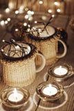 Tazas elegantes de cerámica en suéteres y guirnalda retra de la Navidad en fondo de las luces del bokeh Profundidad del campo baj Fotografía de archivo libre de regalías