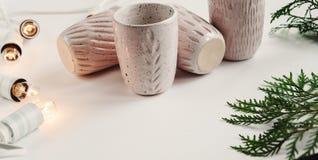 Tazas elegantes de cerámica y guirnalda retra de la Navidad y branc verde Imágenes de archivo libres de regalías