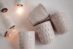 Tazas elegantes de cerámica y guirnalda retra de la Navidad en el backgr blanco Imagen de archivo libre de regalías