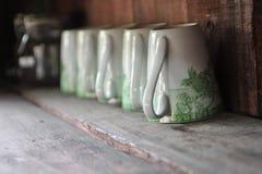 Tazas en el estante de madera Imagen de archivo libre de regalías